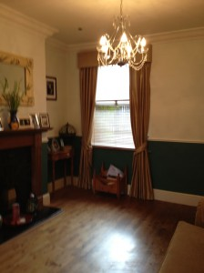 Hard pelmet curtains with tie backs on bay fronted window